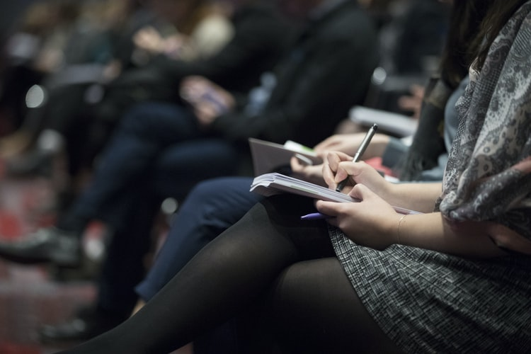 Woman at a conference writing down notes while listening to a speaker.