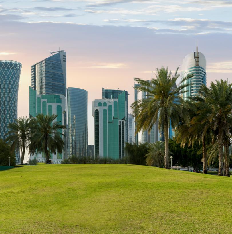 The national flag of Qatar and the skyline of Doha