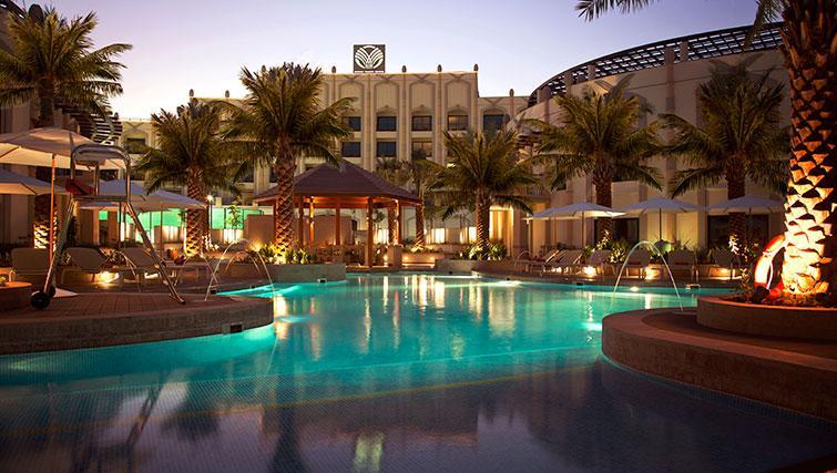Pool area at night at Al Ain Rotana Apartments