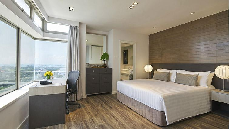 Bed and work space at PARKROYAL Serviced Suites Singapore