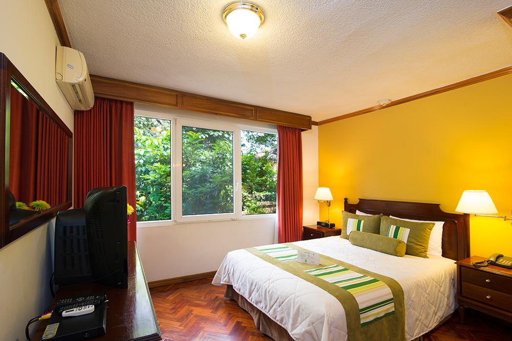 Queen bed at Villas del Rio Aparthotel