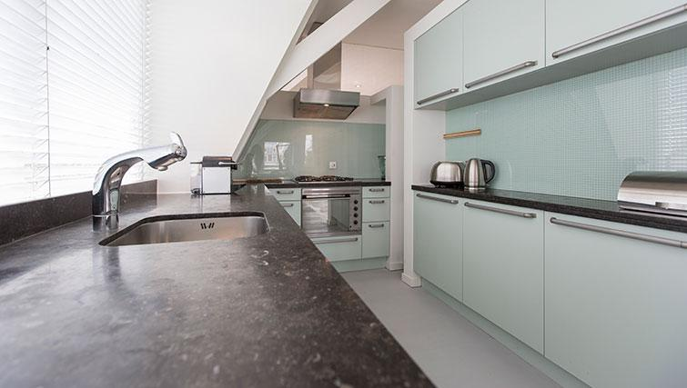 Mint green kitchen at Apartment Amstel View, Amsterdam
